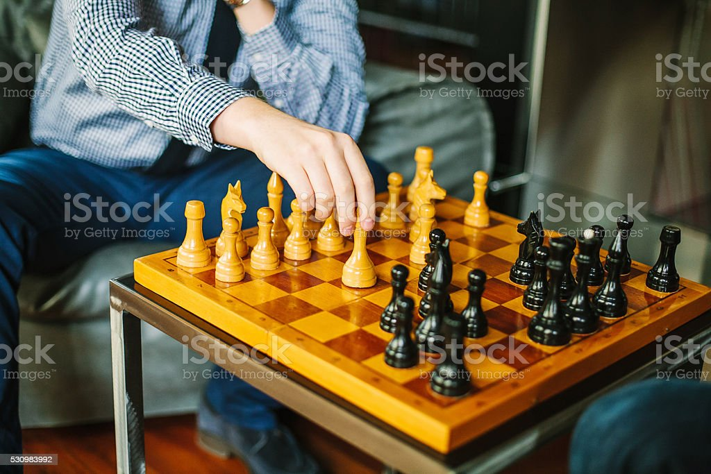 Man in shirt and tie playing chess inside the room. stock photo