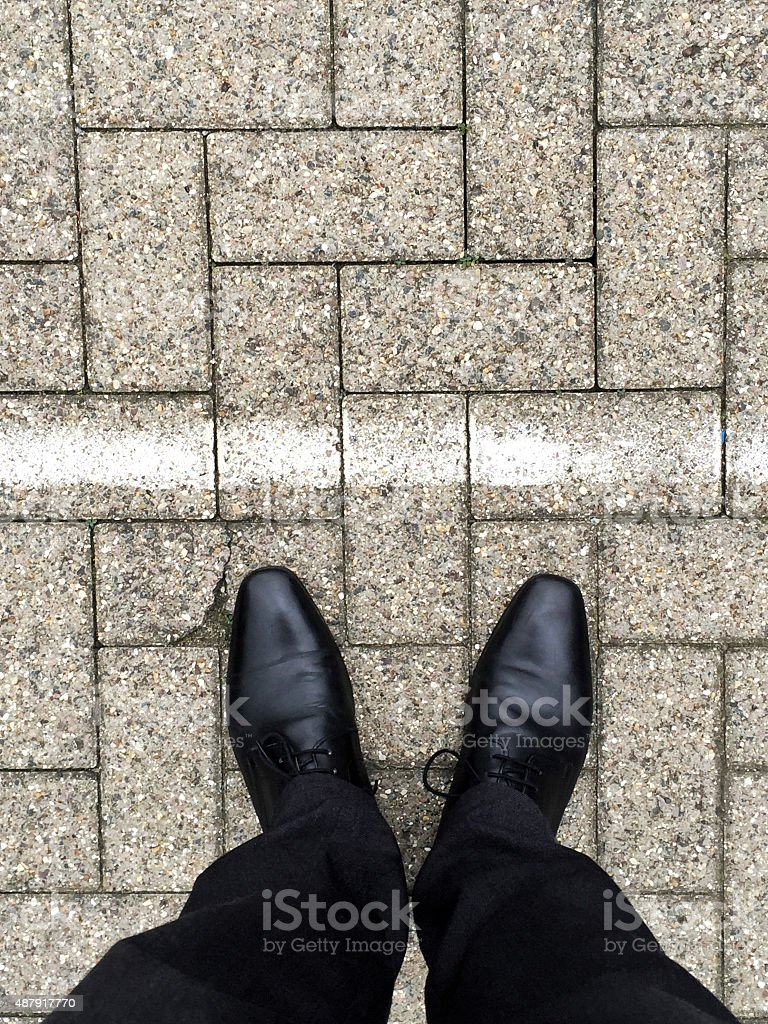 Man in shoes on Pavement stones at white line stock photo
