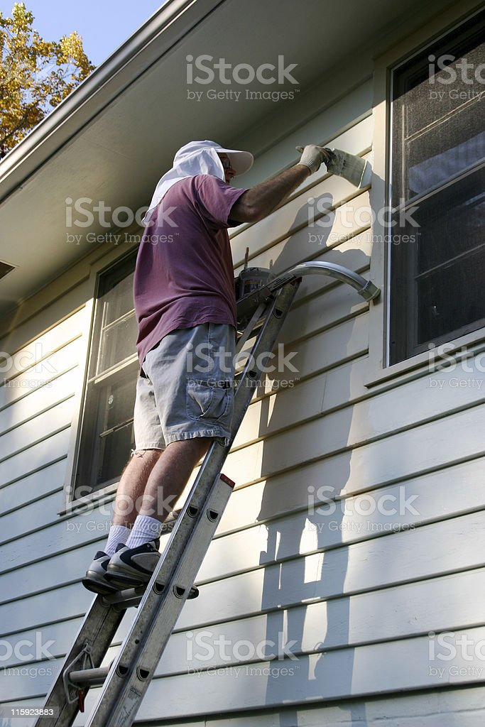 A man in shorts painting a house royalty-free stock photo