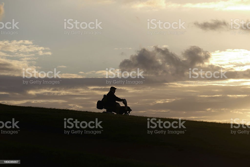 Man in silhouette on mobility scooter stock photo