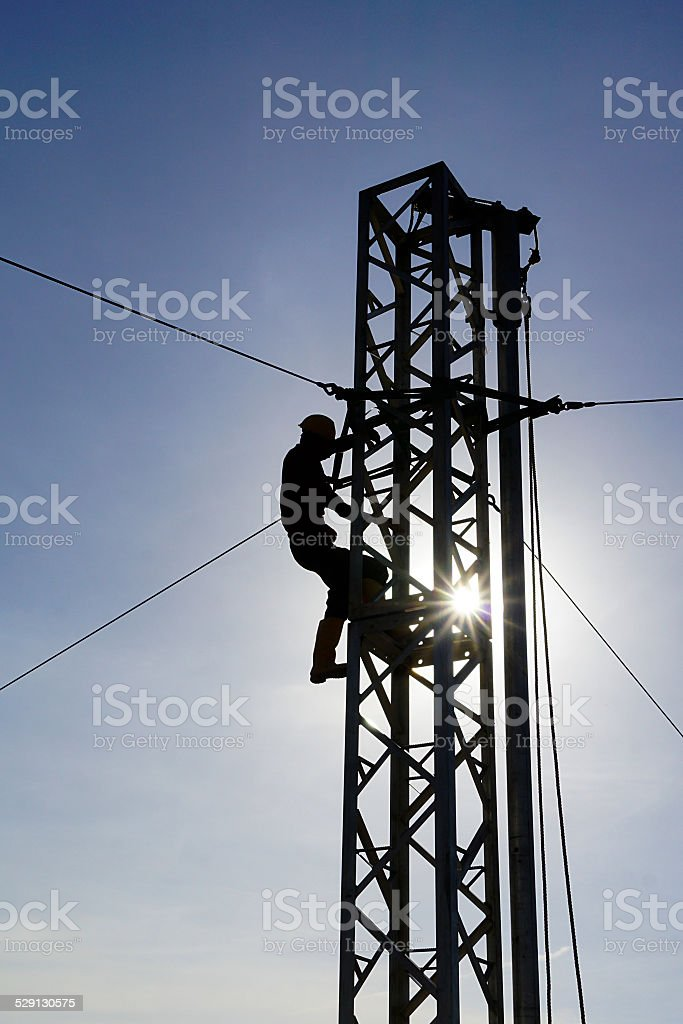 Man in silhoutte working on tower with sun burst stock photo