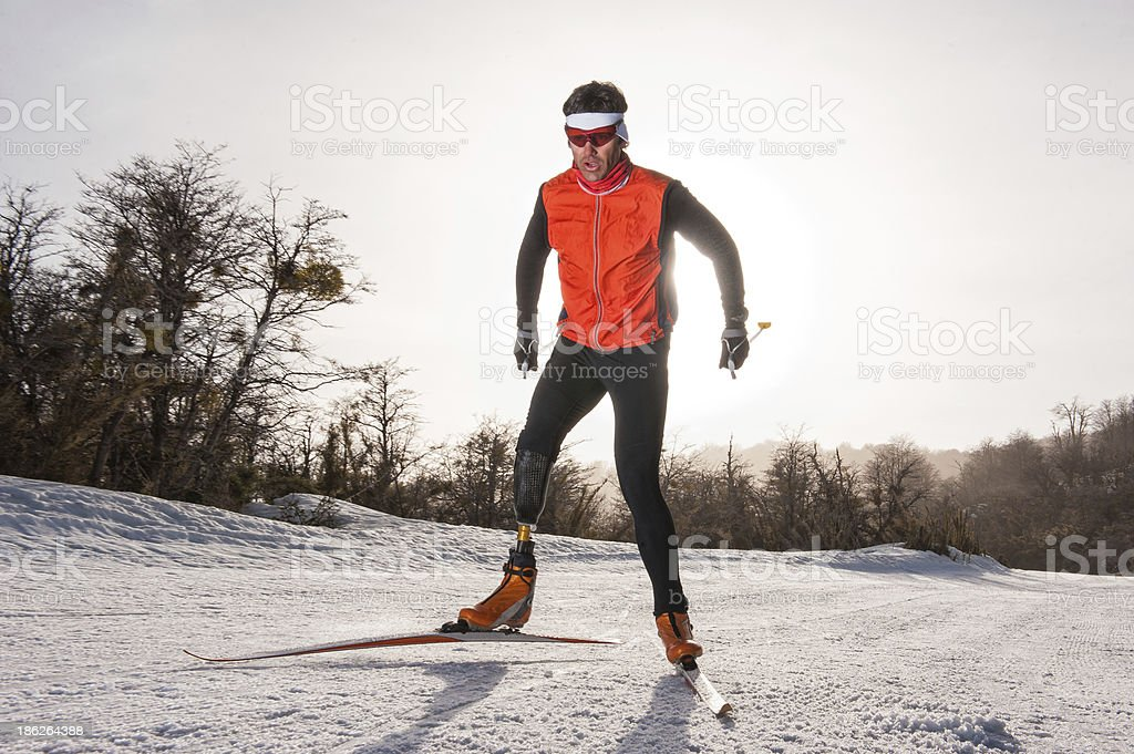 Man in ski suit skiing through snow stock photo