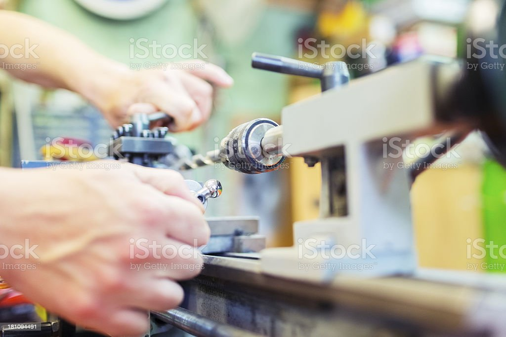 Man in small workshop working with drilling machine royalty-free stock photo