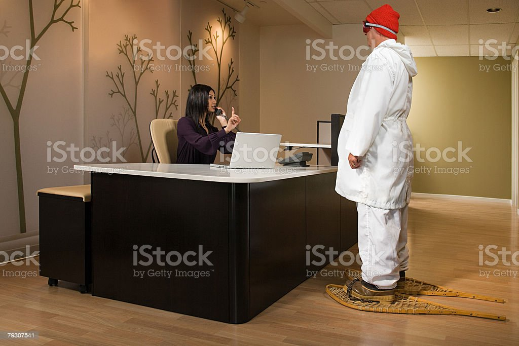 A man in snowshoes waiting for a receptionist stock photo