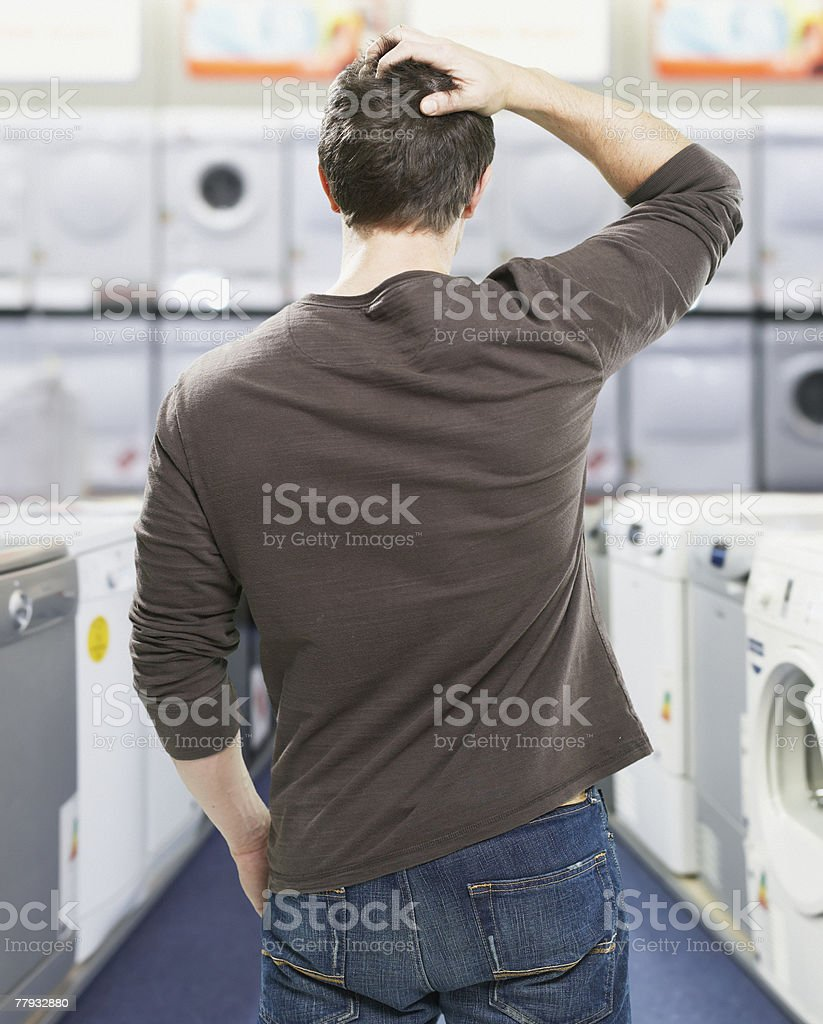 Man in store looking at appliances confused stock photo