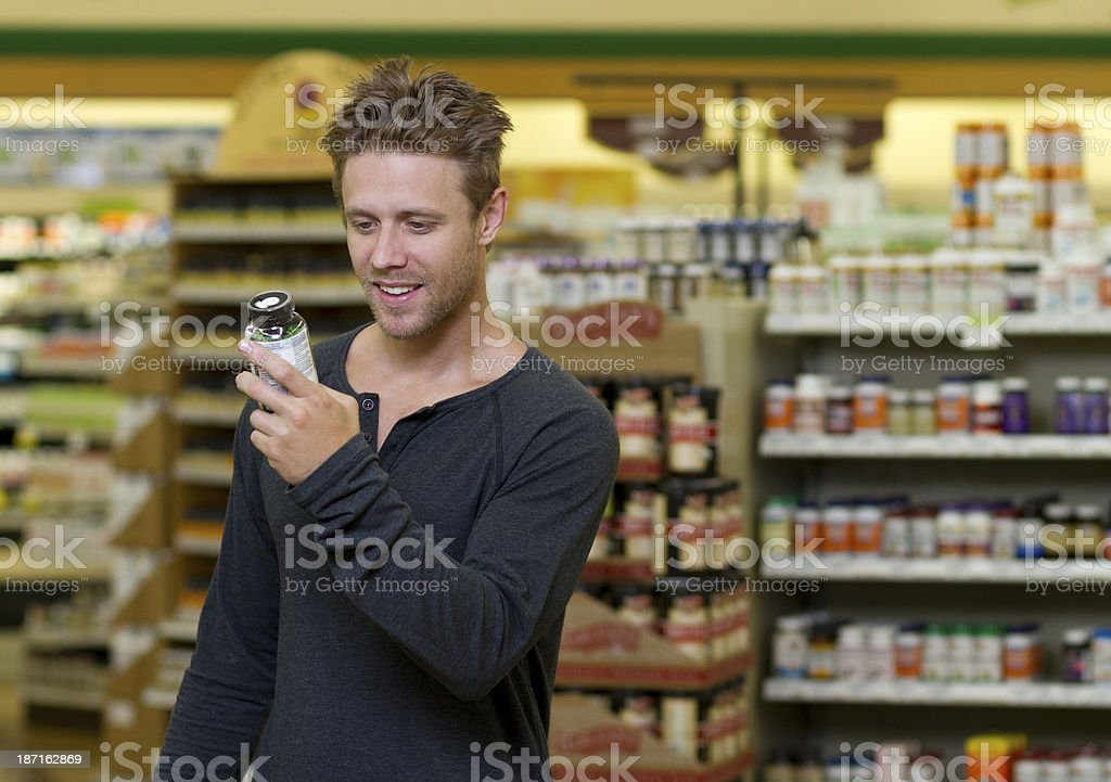 Man in Store Looks at Supplement stock photo