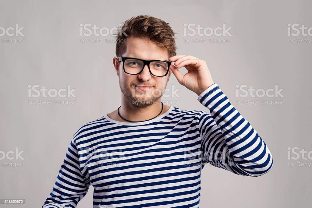 Man in striped t-shirt and eyeglasses against gray background. stock photo