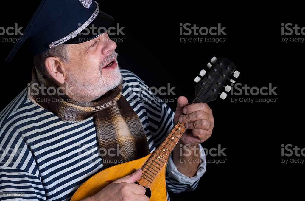 man in striped vest and comforter with mandolin stock photo