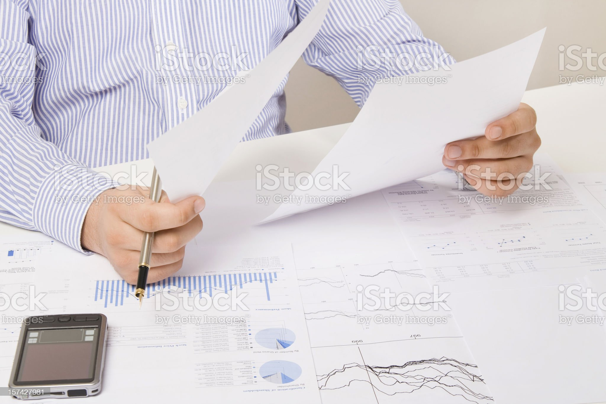 Man in stripped dress shirt analyzing reports royalty-free stock photo