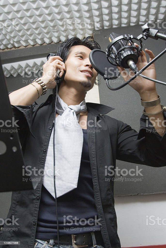Man in studio sings into microphone royalty-free stock photo