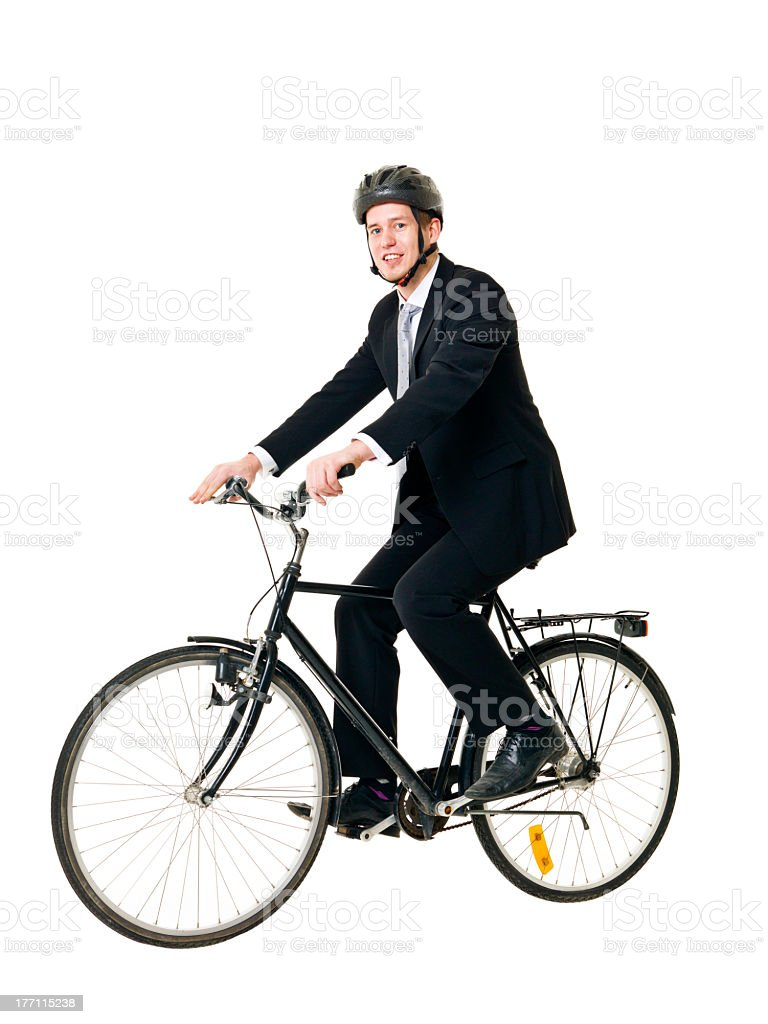 Man in suit and helmet balancing on bicycle stock photo