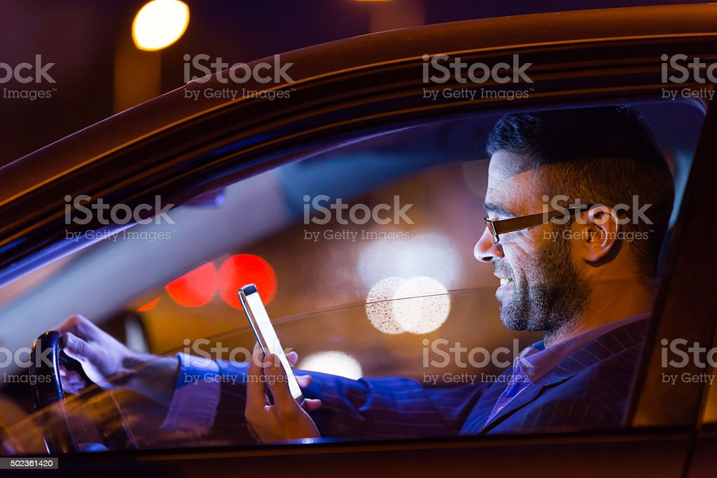 Man in suit at car by the night with phone stock photo