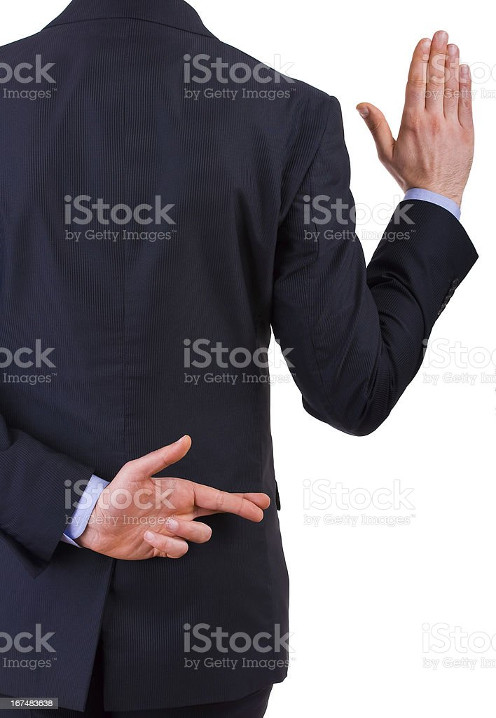 Man in suit crosses fingers behind back while taking oath stock photo