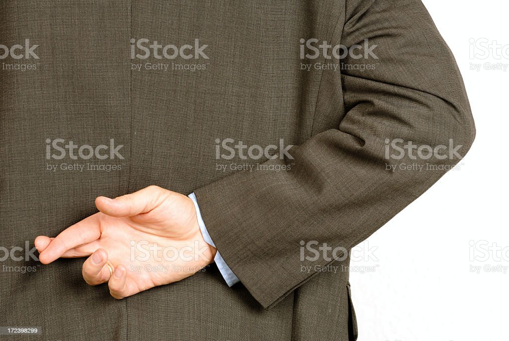 Man in suit crossing his fingers behind his back royalty-free stock photo