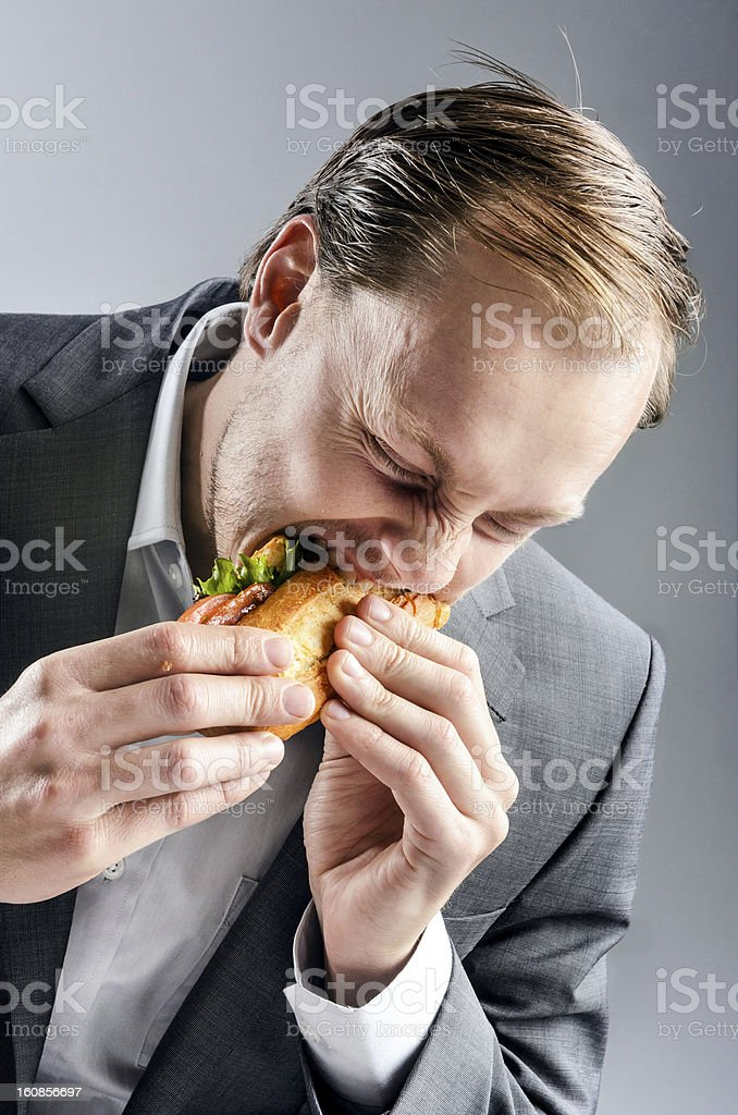 Man in suit eats BLT eagerly stock photo