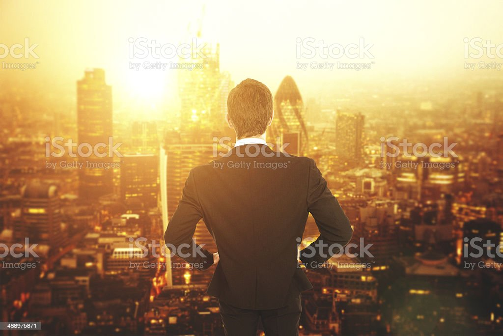 Man in suit facing London skyline stock photo