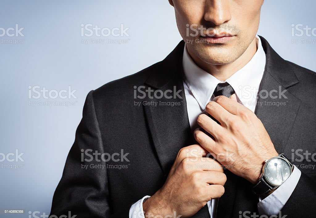 Man in suit fixing his tie stock photo