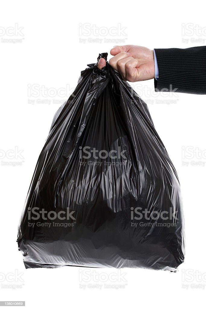 Man in suit holding bag of garbage on a white background stock photo