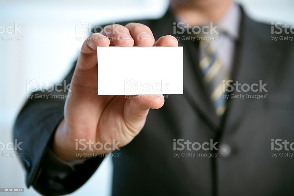 Man in suit holding blank business card in a his hand stock photo