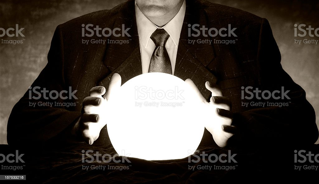 Man in suit holds hands over glowing crystal ball stock photo