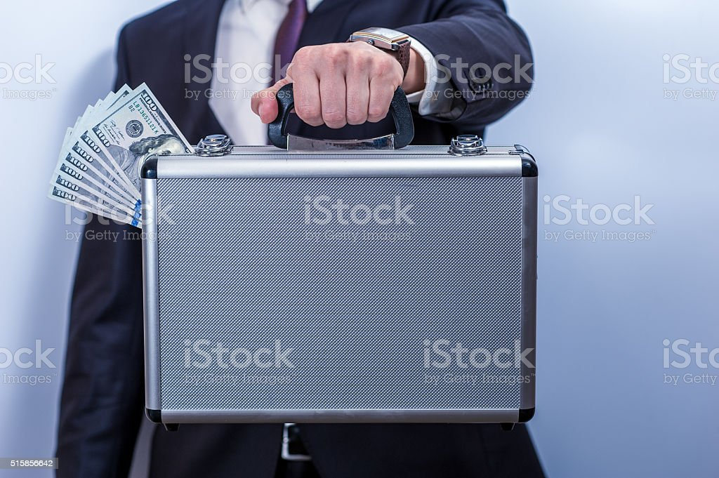 Man in suit holds metal briefcase with dollars stock photo
