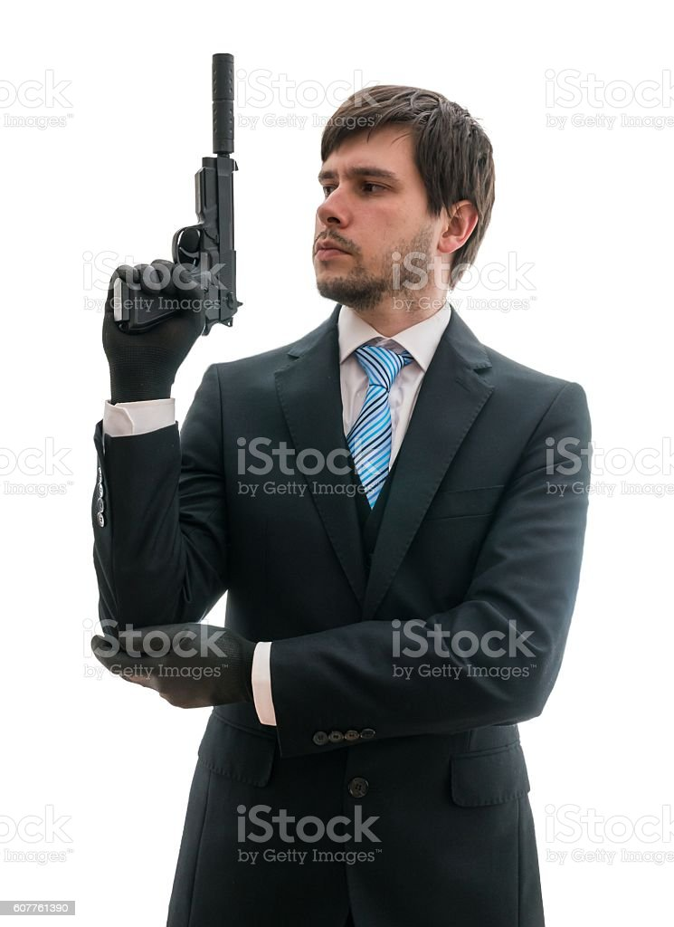 Man in suit holds pistol with silencer in hand. stock photo