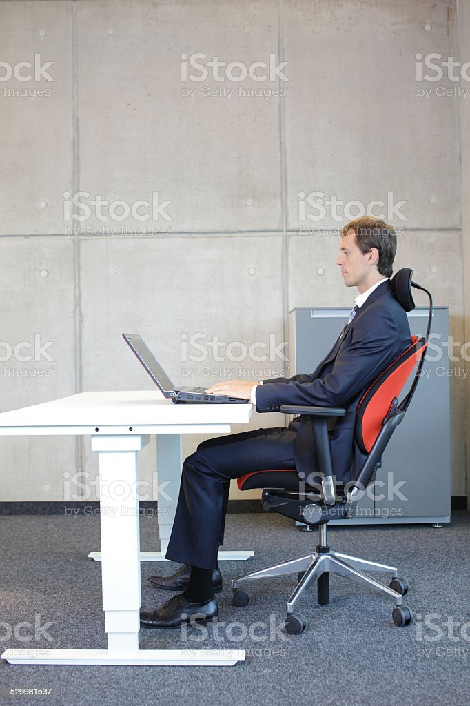 man in suit in correct sitting position at workstation in office stock photo