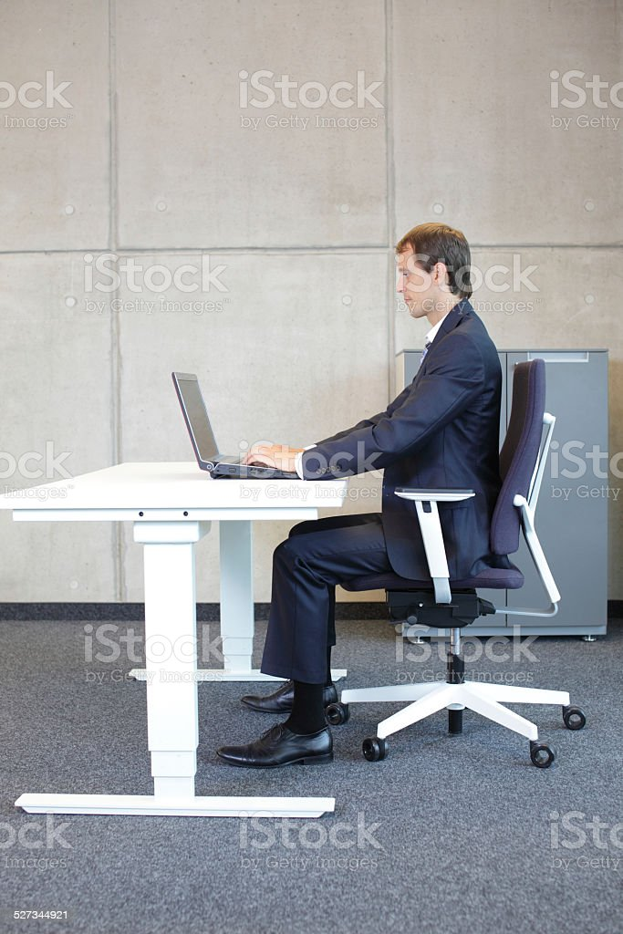man in suit in correct sitting position at workstation stock photo