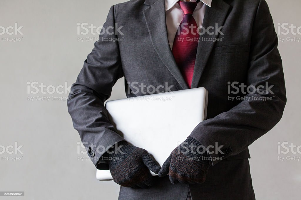 Man in suit is stealing a laptop stock photo