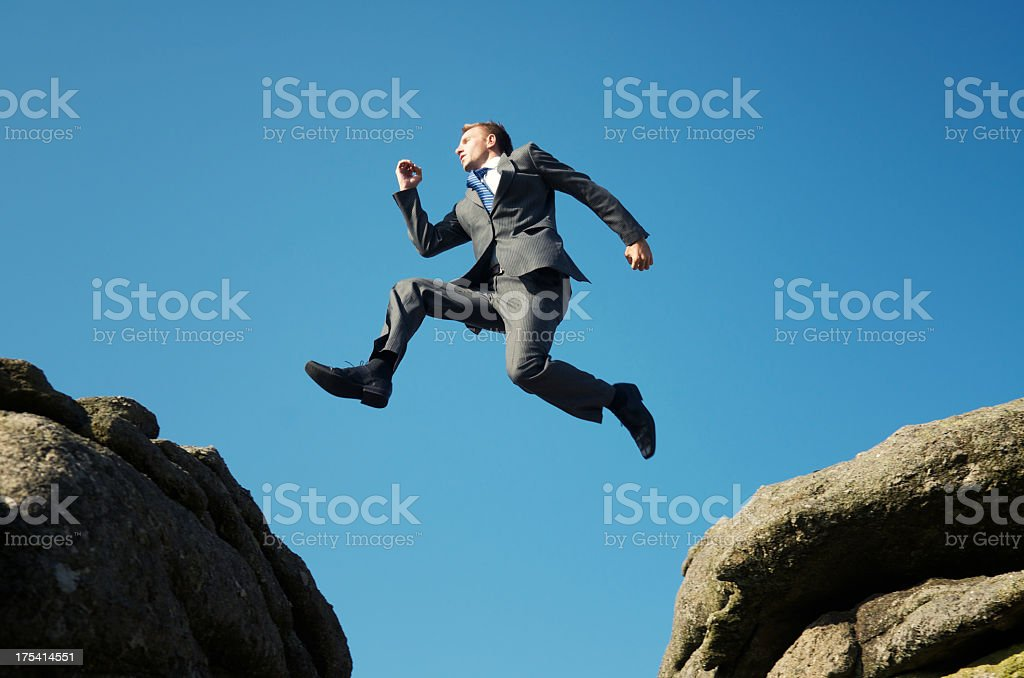 Man in suit jumping between towering rocks stock photo
