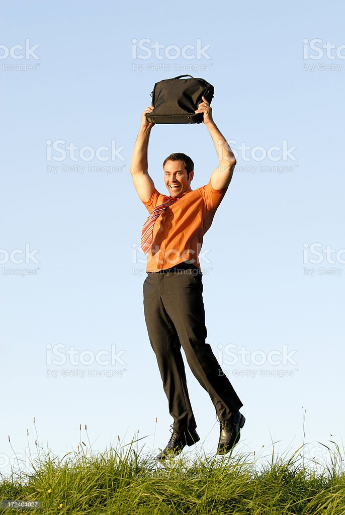 Man in suit jumping with briefcase over grass royalty-free stock photo