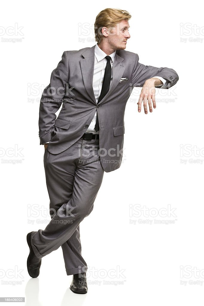 Man in Suit Leans Against Nothing stock photo