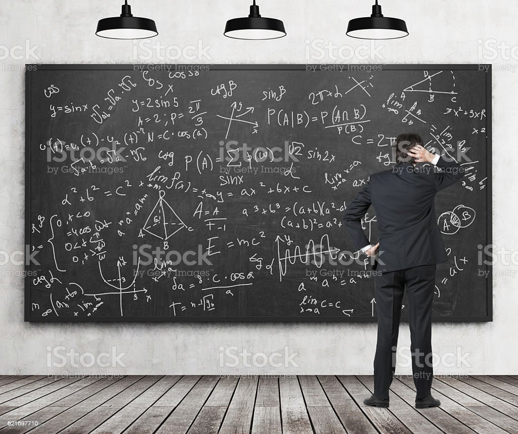 Man in suit looking at blackboard with formulas stock photo