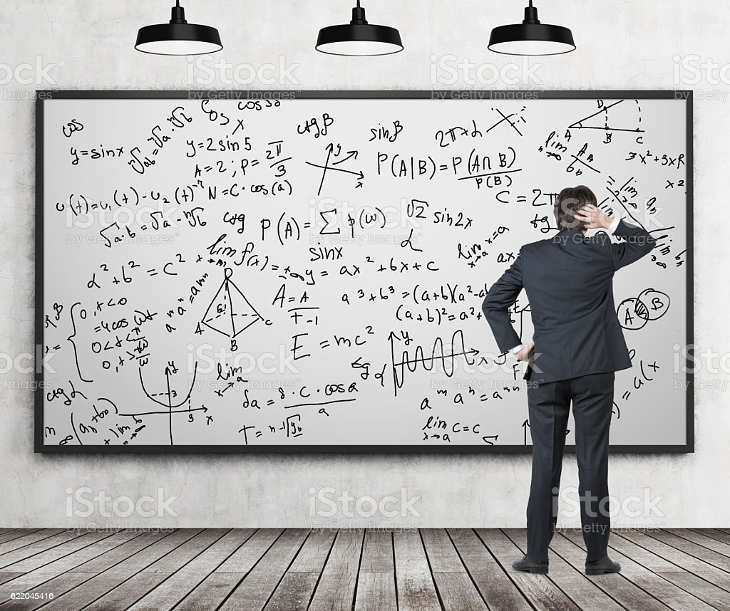 Man in suit looking at whiteboard with formulas stock photo