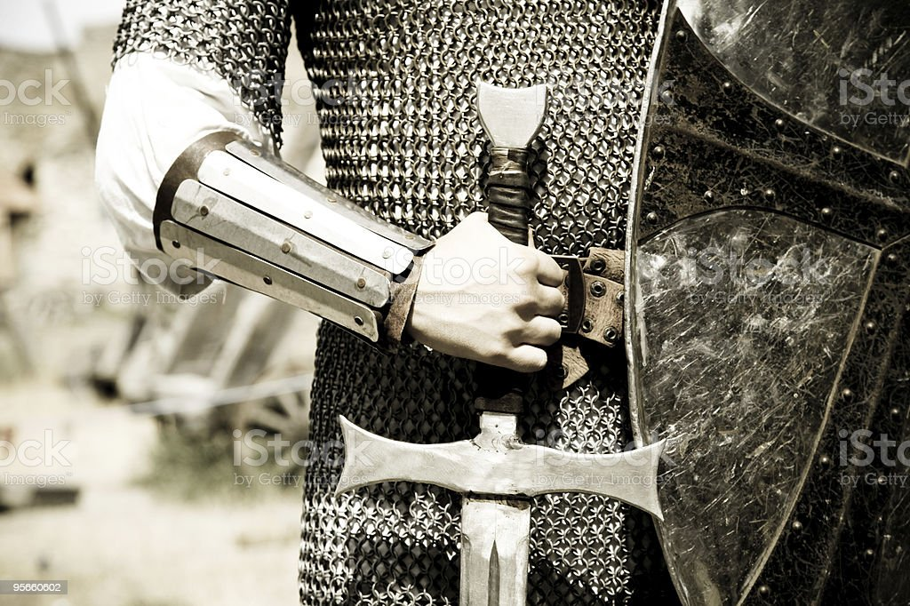 Man in suit of armor with medieval sword stock photo