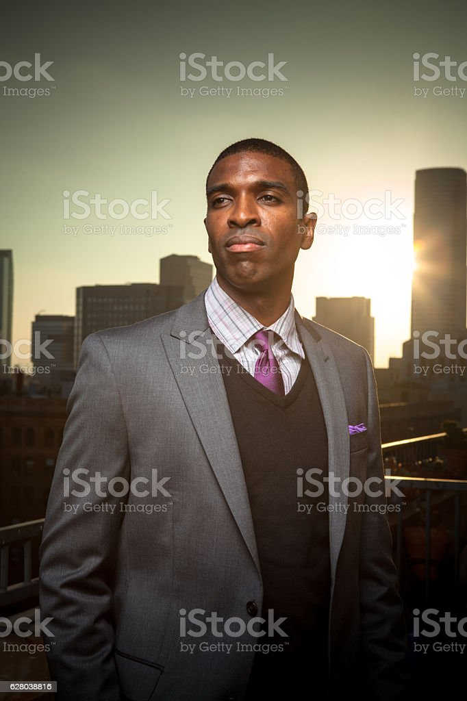 Man in Suit on Balcony at Sunset stock photo