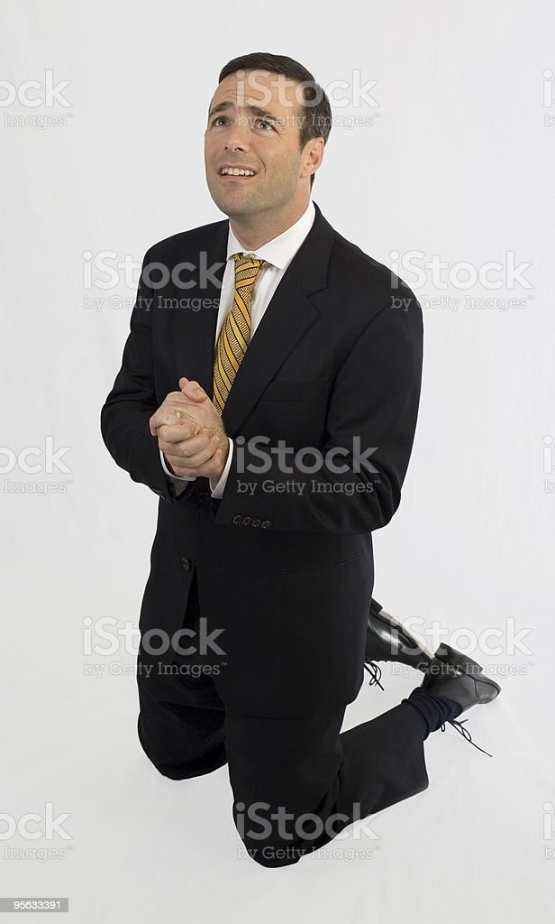Man in suit on knees begging stock photo