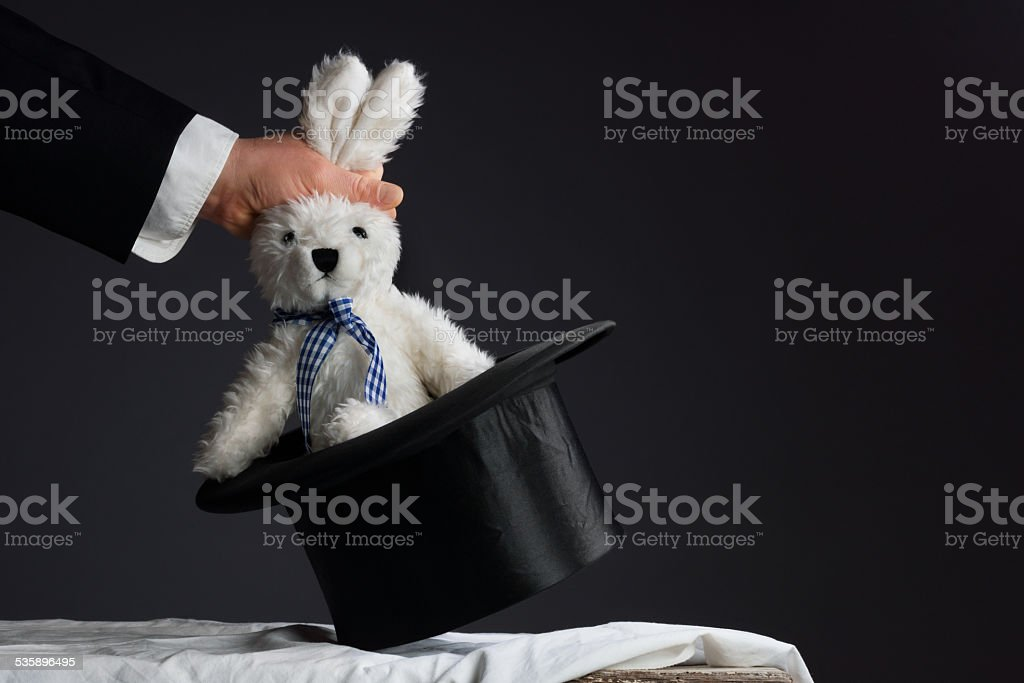 Man in suit pulling a rabbit out of the hat stock photo
