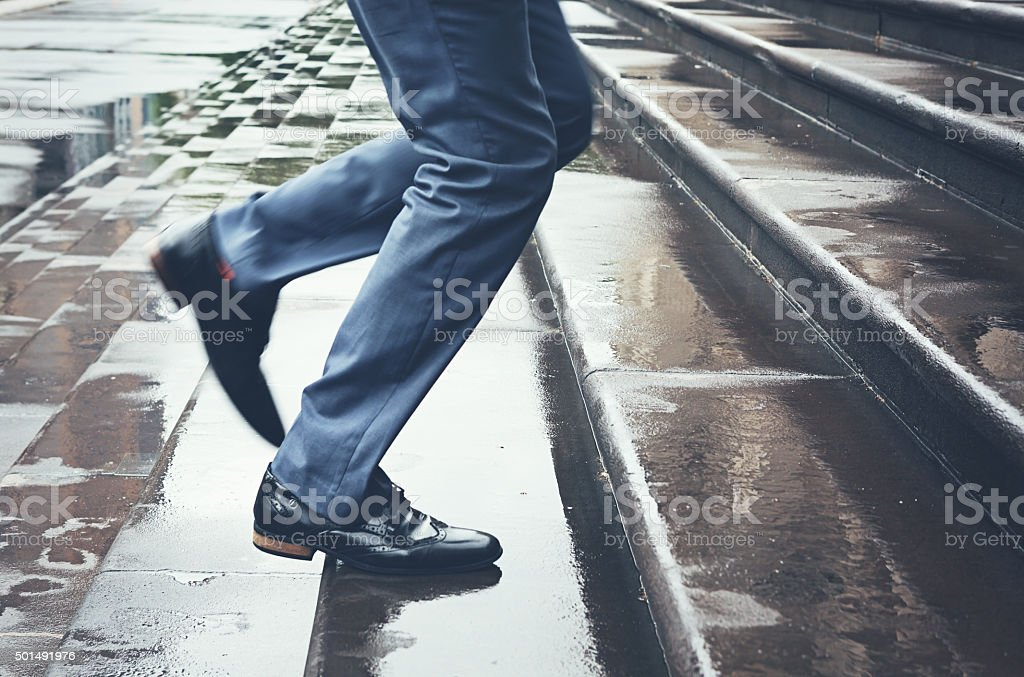 Man in suit running late up steps in rain stock photo