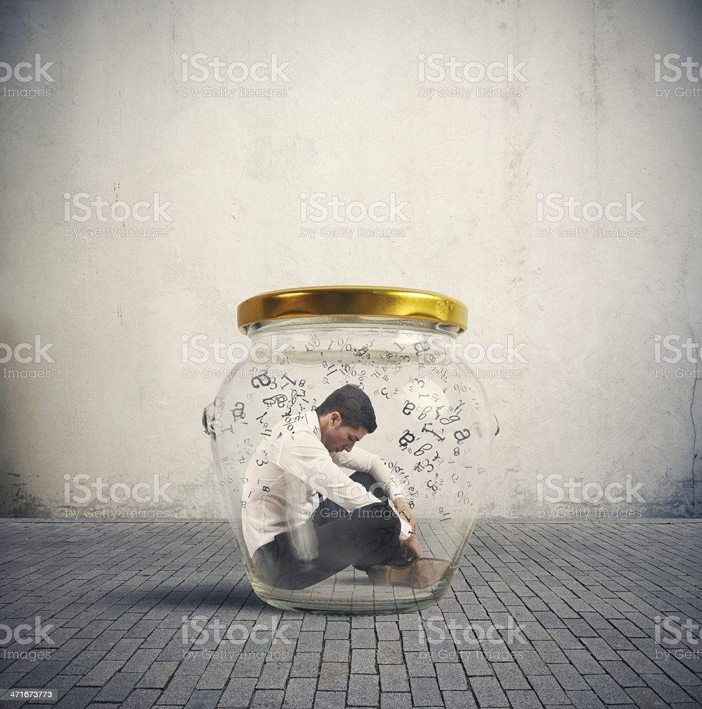 Man in suit sitting in a glass jar stock photo
