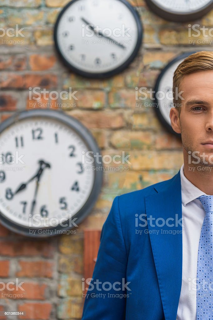 Man in suit standing near wall with clocks stock photo