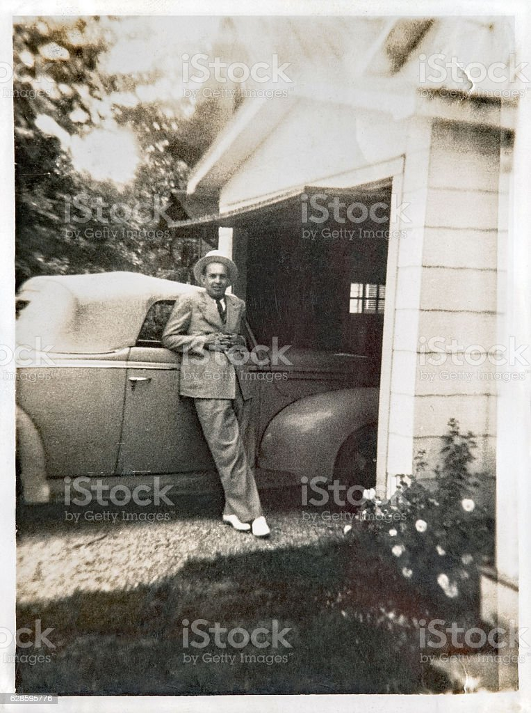 Man in Suit & Straw Hat by Convertible Car stock photo