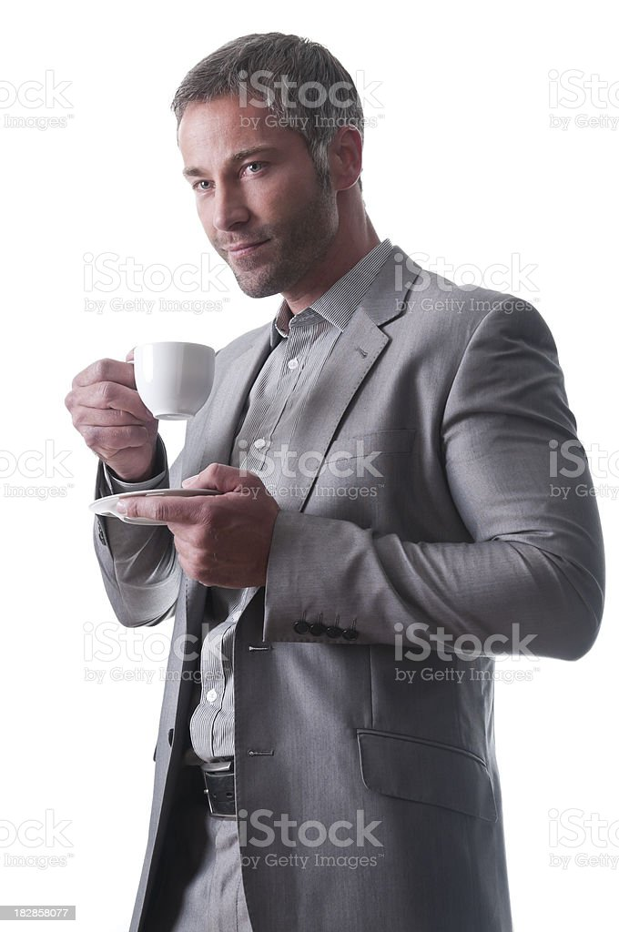 Man in suit with no tie drinks coffee and smiles. royalty-free stock photo