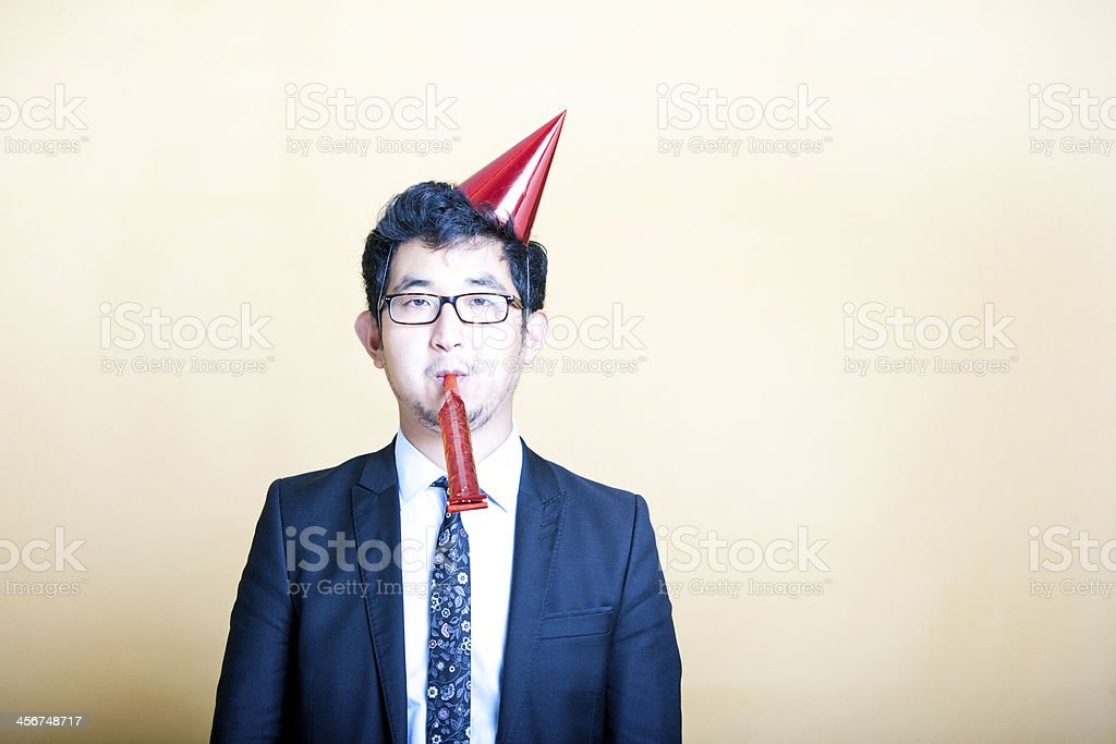 Man in suit with red party hat on and blowing party whistle stock photo