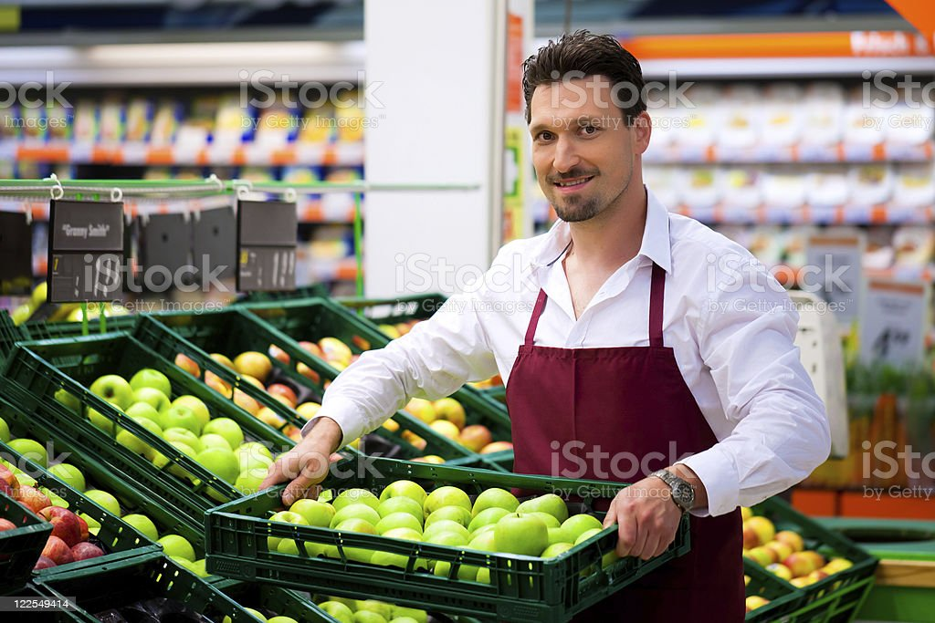 Man in supermarket as shop assistant stock photo