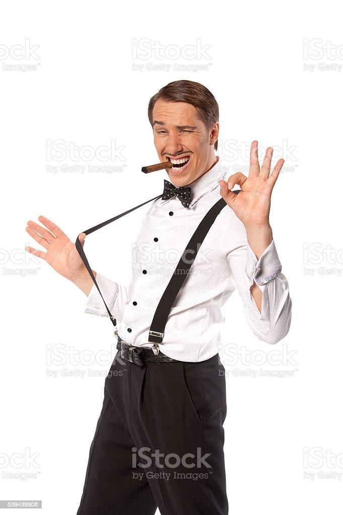 Man in suspenders smoke a cigar. stock photo