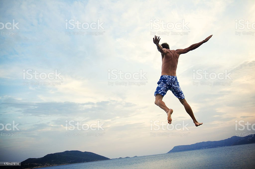 Man in Swimming Trunks Jumps into Sea at Dusk royalty-free stock photo