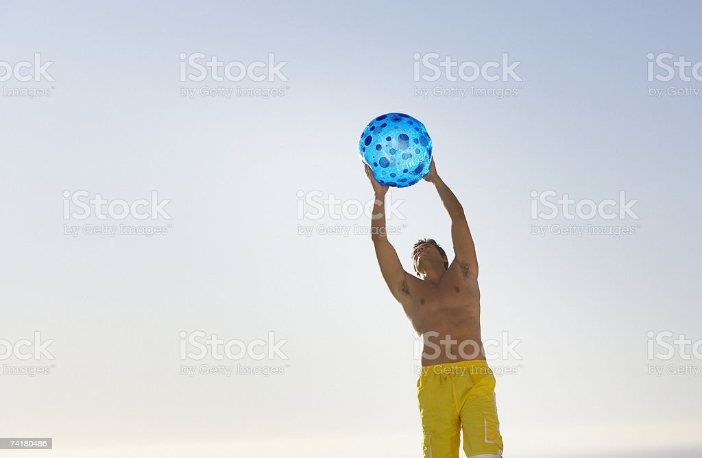 Man in swimsuit with beach ball outdoors royalty-free stock photo