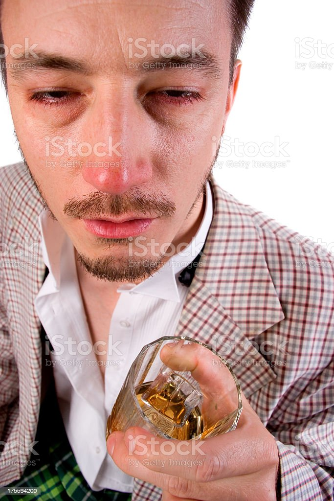 A man in tartan holding a whisky glass and looking drunk stock photo