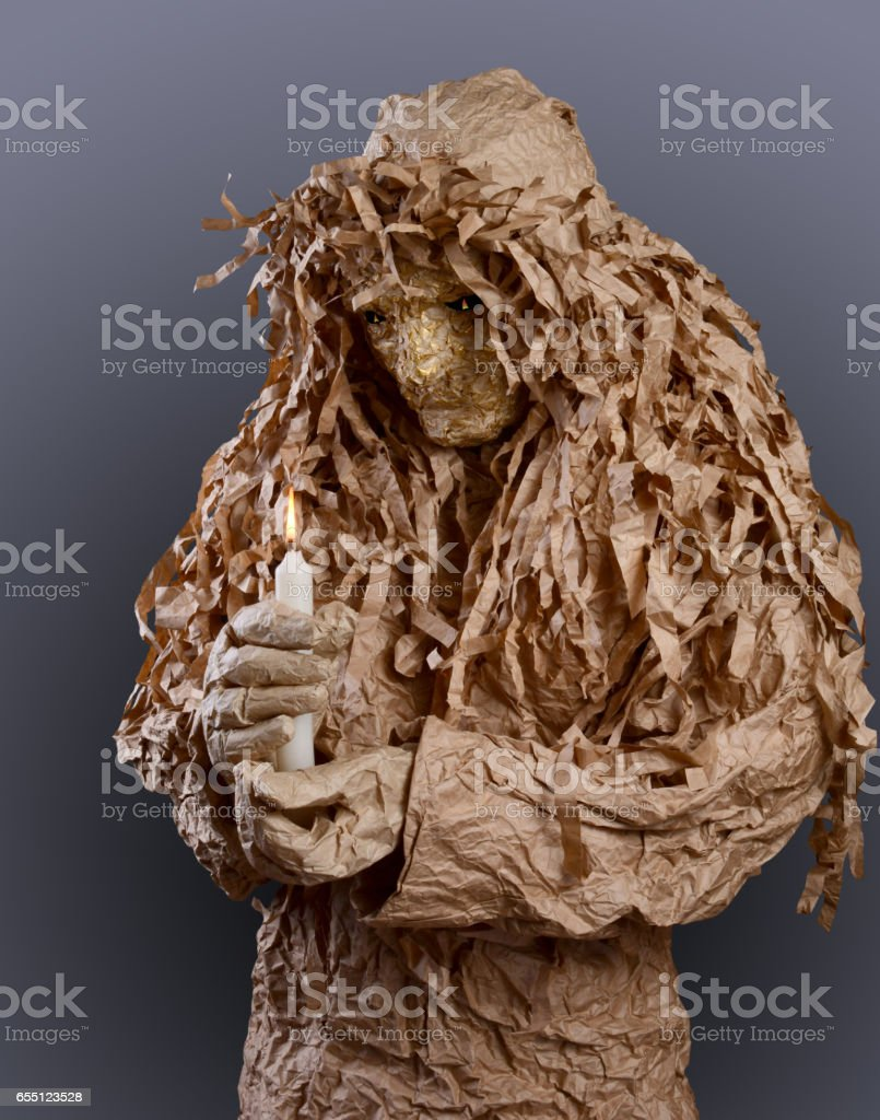 man in terrible mask holding a burning candle stock photo